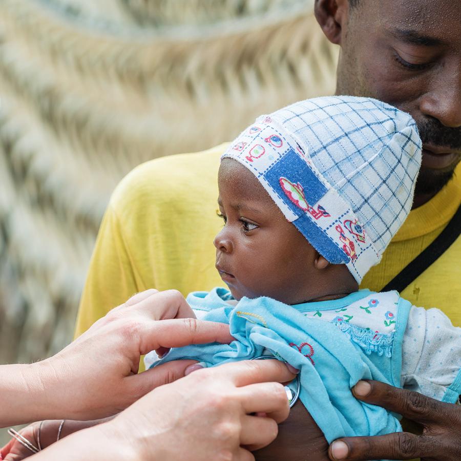 Ärztin untersucht Baby in Afrika