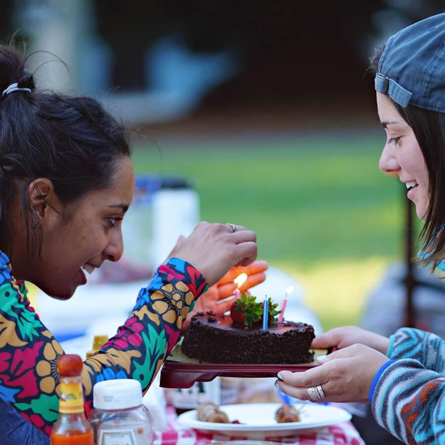 Zwei Mädchen dunkel- und hellhäutig mit Kuchen