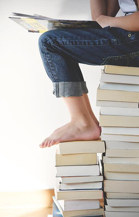 Person sitzt auf Buchstapel